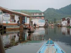 Shikara glides past shops on the Dal Lake